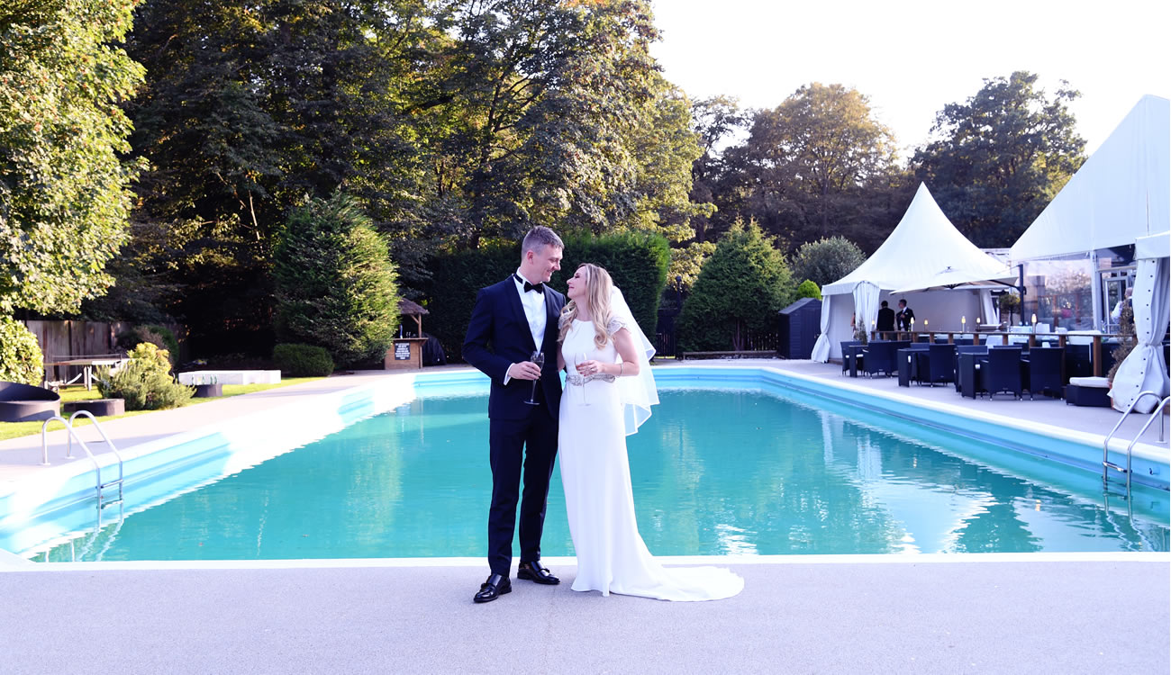 Beautiful Bride & Groom Kissing next to our pool here at the Kings Oak Epping Forest